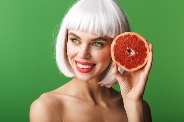 Piękne zdrowe młode kobiety topless na sobie krótkie białe włosy stojąc na białym tle, pokazując plasterki grejpfruta