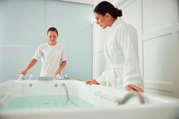 Piękne, zdrowe, uśmiechnięte kaukaski kobieta robi zabiegi kosmetyczne w salonie spa i opieki zdrowotnej