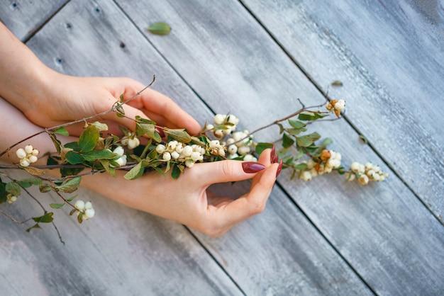 Piękne żeńskie ręki kłamają z kwiatami na drewnianym tle, ręki opieka nad skórą, piękny manicure