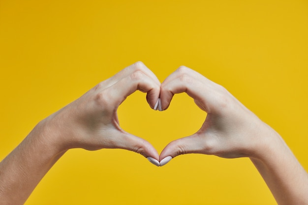Piękne żeńskie ręki robi sercu podpisywać