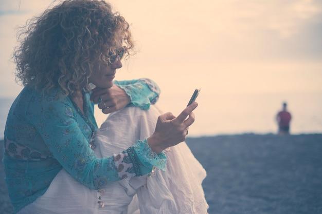 Piękne zimne odcienie kobieta w średnim wieku korzysta z technologii telefonu komórkowego na zewnątrz z ubraniami w stylu shabby chic. omage koncepcyjne w odcieniach niebieskiego dla niezależnych kobiecych i internetowych profili w mediach społecznościowych