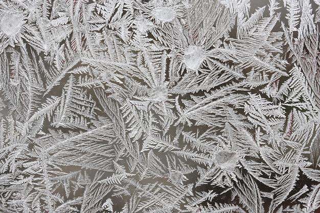 Piękne zimowe tło, szron na oknie, naturalna faktura na szkle z zamrożonym wzorem.