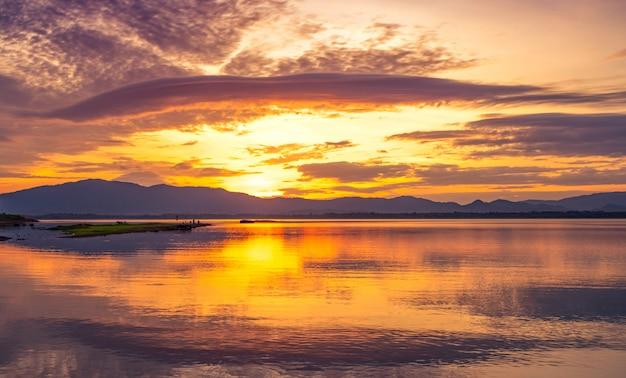 Piękne złote niebo rano z wschodem słońca nad pasmem górskim oraz jeziorem lub rzeką. krajobraz zbiornika i góry.