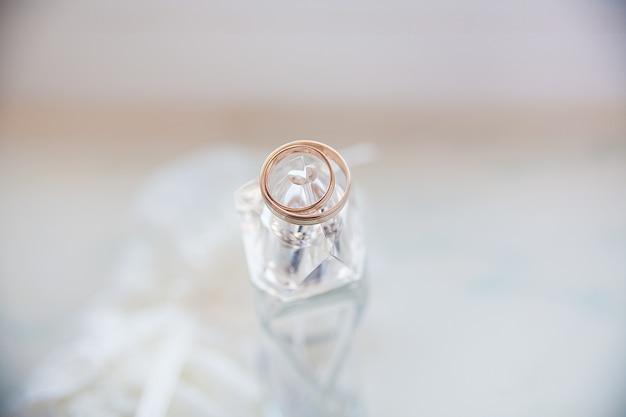 Piękne złote pierścienie leżą na słoiku perfum