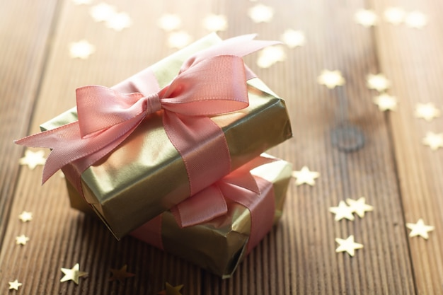 Piękne złote prezenty boże narodzenie, impreza, urodziny. świętuje shinny niespodziankę boksuje copyspace drewnianego tło