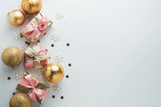 Piękne złote prezenty gloden bombki na białym tle. boże narodzenie, impreza, urodziny. świętuj shinny niespodziankę pudła copyspace. kreatywny widok płasko leżał z góry.