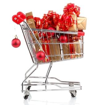 Piękne złote prezenty z czerwoną wstążką i bombkami w koszyku na białym tle