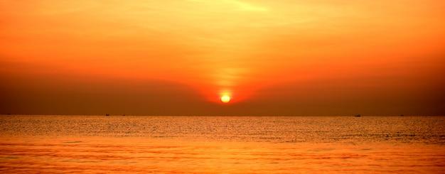 Piękne złote żółte niebo i słońce wzrasta widok na plażę, plażę i leżaki. piękny złoty żółty niebo i słońce