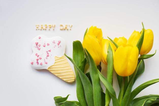 Piękne żółte tulipany i ciasteczko z napisem happy day
