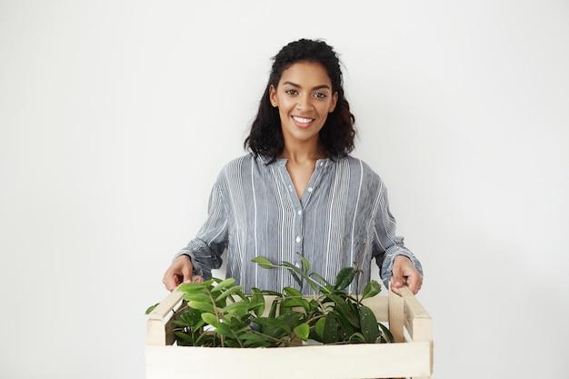 Pięknego afrykańskiego kobieta botanika mienia uśmiechnięty pudełko z roślinami.