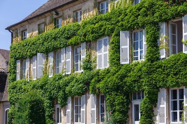 Pięknego antykwarskiego starego cegła domu nieociosany okno z białymi drewnianymi żaluzjami