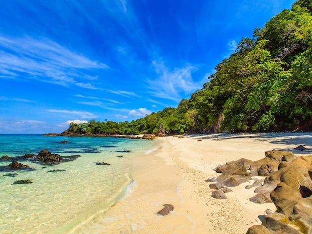 Pięknego białego piaska tropikalny beack z błękitnym morzem i niebem