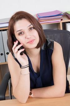Pięknego bizneswomanu pracujący obsiadanie przy jej biurkiem na telefonie