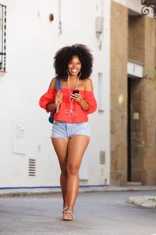 Pięknego ciała piękna rozochocona kobieta chodząca z telefonem komórkowym i słuchawkami