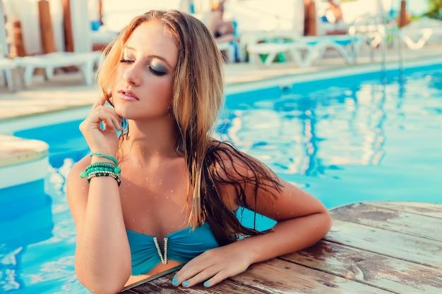 Pięknego długie włosy kobiety wzorcowy pozować basenem, plenerowy portret