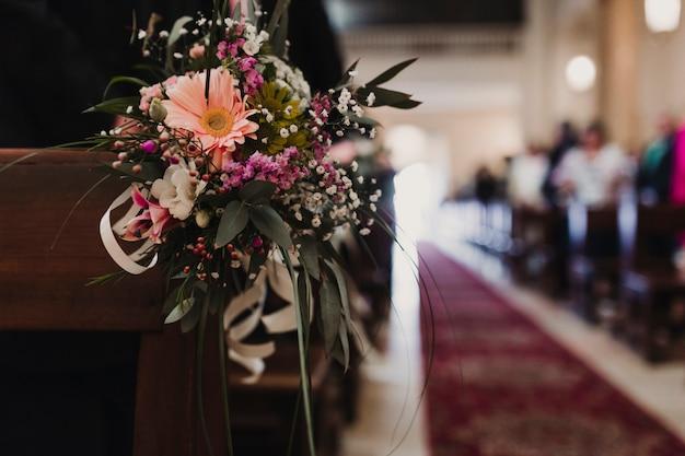 Pięknego kwiatu ślubna dekoracja w kościół. selektywne ustawianie ostrości. nierozpoznawalni goście w tle. koncepcja małżeństwa w kościele