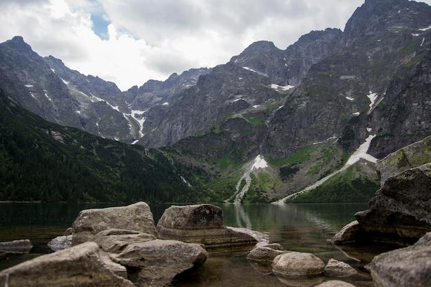 Pięknego lata alpejski halny jeziorny widok zakrywający w zielonych drzewach z kamieniami z przodu i chmurnieje w niebie. odbicie góry w wodzie. krystalicznie czysta woda. europa, alpy.