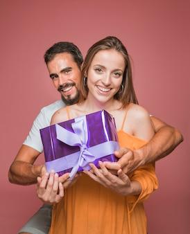 Pięknego pary mienia prezenta purpurowy pudełko przeciw barwionemu tłu