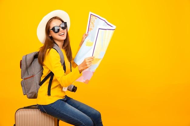 Pięknego podróżnika azjatykcia kobieta z podróżnym wyposażeniem