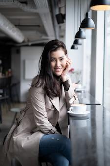 Pięknego portreta azjatycki dziewczyny obsiadanie na kontuaru barze w sklep z kawą kładzenia ręce na jej podbródku patrzeje kamerę z uśmiechem.