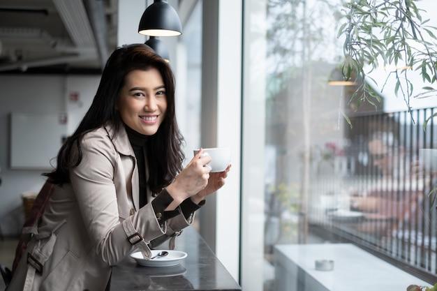 Pięknego portreta azjatycki dziewczyny obsiadanie na kontuaru barze w sklep z kawą trzyma filiżankę z uśmiechem patrzeje kamerę.
