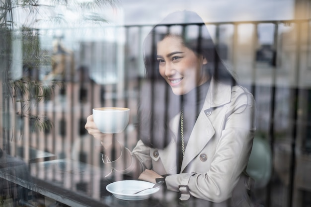 Pięknego portreta azjatycki dziewczyny obsiadanie na kontuaru barze w sklep z kawą trzyma filiżankę z uśmiechem patrzeje outside.