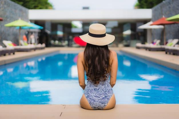 Pięknego portreta azjatykcia kobieta relaksuje szczęśliwego uśmiech wokoło plenerowego pływackiego basenu