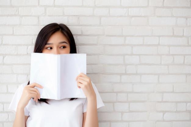 Pięknego portreta azjatykciej kobiety szczęśliwy chować za otwiera książkę