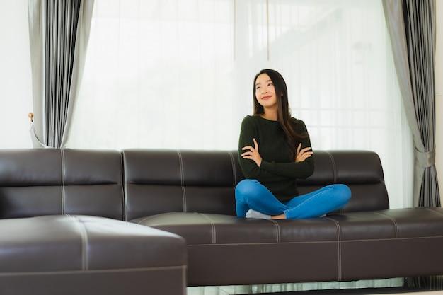Pięknego portreta młoda azjatykcia kobieta siedzi relaksuje na kanapie