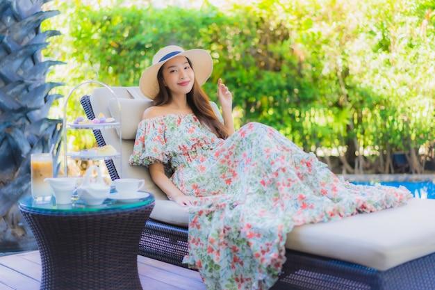 Pięknego portreta młoda azjatykcia kobieta z popołudniowym herbacianym ustawiającym z kawą siedzi na krześle wokoło pływackiego basenu