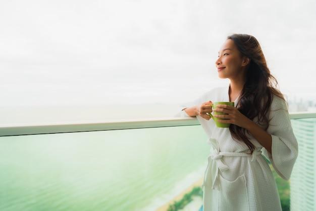Pięknego portreta młode azjatykcie kobiety trzyma filiżankę przy plenerowym balkonem z dennym widok na ocean