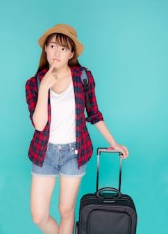 Pięknego portreta młodej azjatykciej kobiety pomysłu myśląca podróż w wakacje z bagażem odizolowywającym na błękitnym tle.