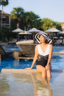 Pięknego portreta młodej azjatykciej kobiety szczęśliwy uśmiech relaksuje wokoło pływackiego basenu w hotel w kurorcie