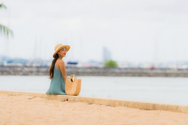 Pięknego portreta młodych azjatykcich kobiet szczęśliwy uśmiech relaksuje wokoło plażowego dennego oceanu