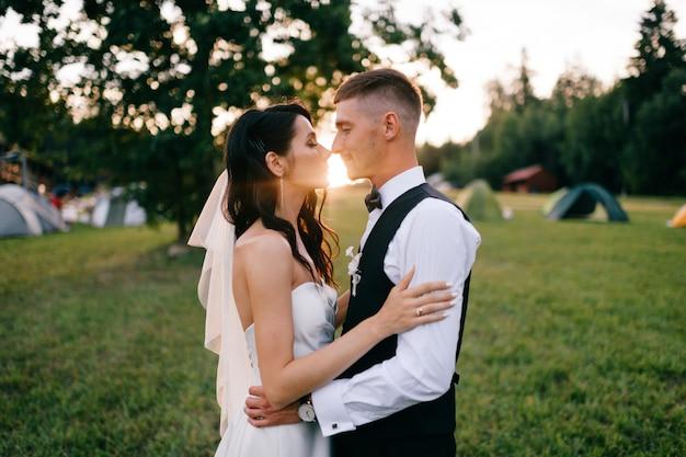 Pięknego ślubu pary plenerowy portret. młody ładny panny młodej przytulenia fornal przy zmierzchem przeciw encapement
