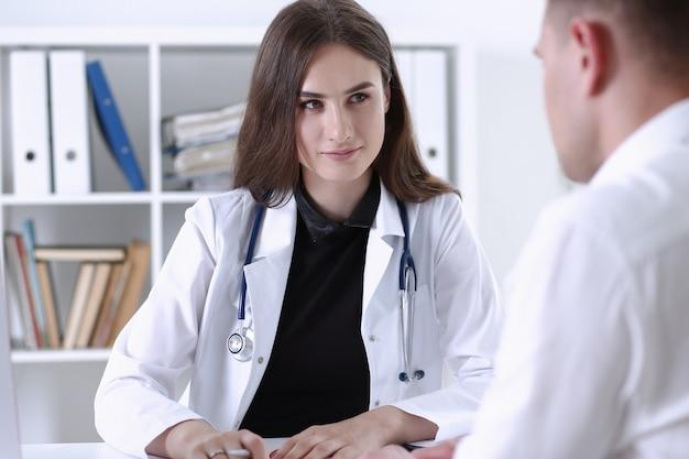 Pięknego uśmiechniętego kobiety lekarki chwyta srebny pióro