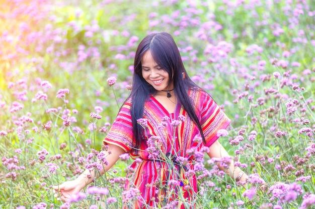 Pięknego uśmiechu azjatykcie kobiety w kwiatu verbena bonariensis ogródzie przy monjam, chiang mai, tajlandia