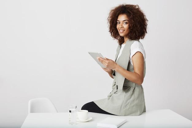 Pięknej afrykańskiej dziewczyny mienia pastylki uśmiechnięty obsiadanie przy miejscem pracy. skopiuj miejsce