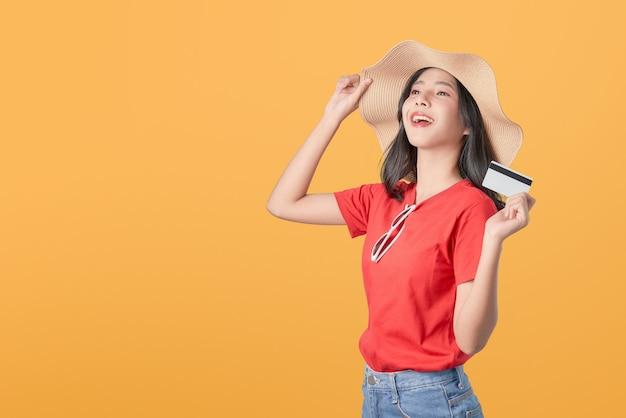 Pięknej azjatyckiej kobiety dobra skóra jest ubranym kapeluszową trzyma kredytowej karty zapłatę na pomarańczowym tle.