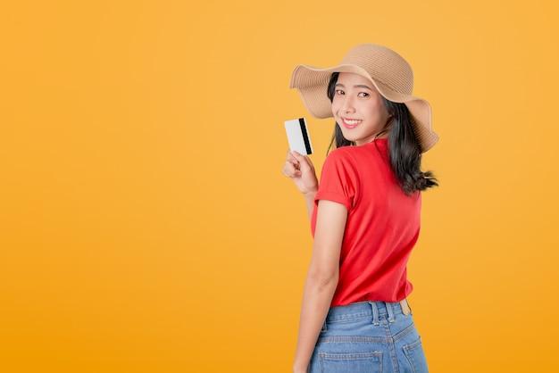 Pięknej azjatyckiej kobiety dobra skóra trzyma płatność kartą kredytową