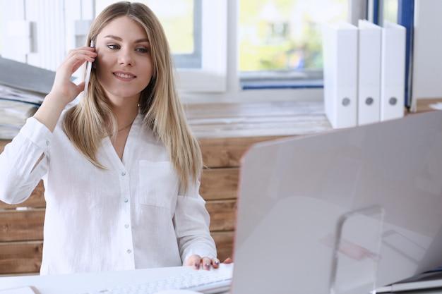 Pięknej blondynki bizneswomanu uśmiechniętego rozmowy telefon komórkowy