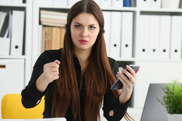 Pięknej brunetki bizneswomanu uśmiechnięty chwyt w ręka telefonie komórkowym