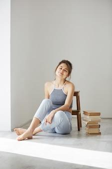 Pięknej czułej kobiety uśmiechnięty obsiadanie na podłoga z książkami nad biel ścianą.