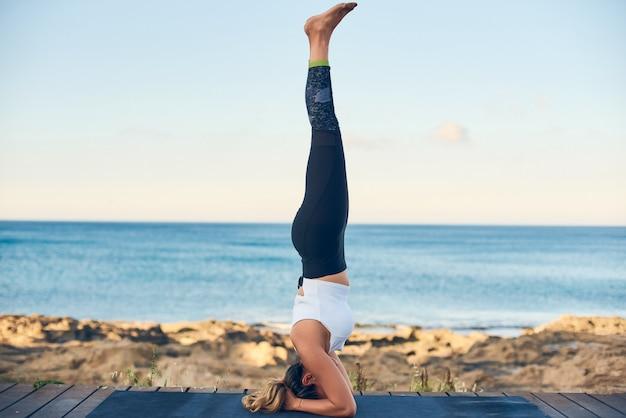 Pięknej dysponowanej kobiety ćwiczy joga przeciw błękitnej dennej pozyci w headstand pozie.