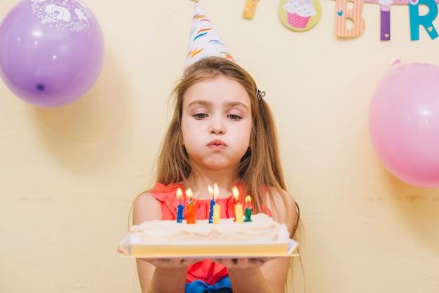 Pięknej dziewczyny podmuchowe świeczki na torcie