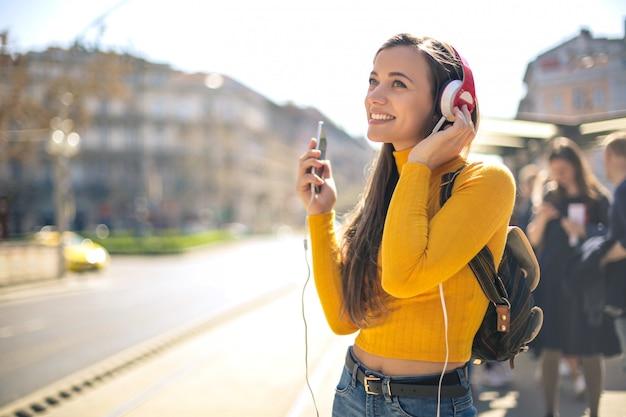 Pięknej dziewczyny słuchająca muzyka z hełmofonem podczas gdy chodzący w ulicie