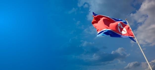 Pięknej flagi państwowej korei północnej na błękitne niebo