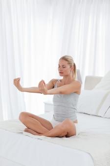 Pięknej kobiety ćwiczy joga na jej łóżku