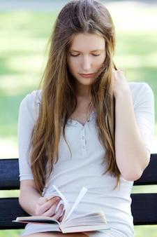 Pięknej kobiety czytelnicza książka w parku