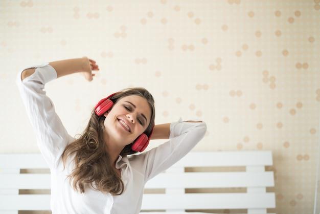 Pięknej kobiety słuchająca muzyka w ranku obsiadaniu na łóżku w domu